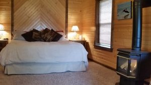 cabin-king-bed-wood-stove-window-horns-ferry-hideaway